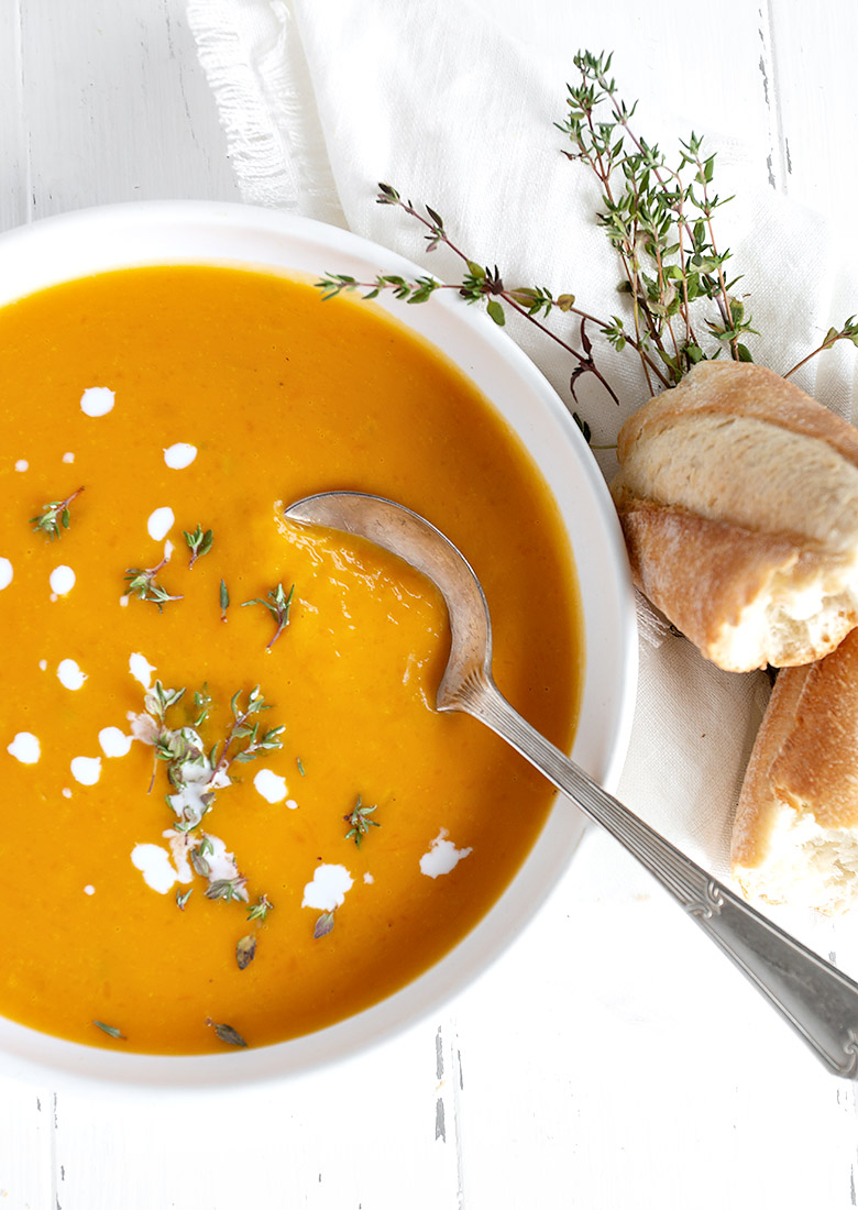 roasted butternut squash soup in white bowl with cream drops and thyme leaves