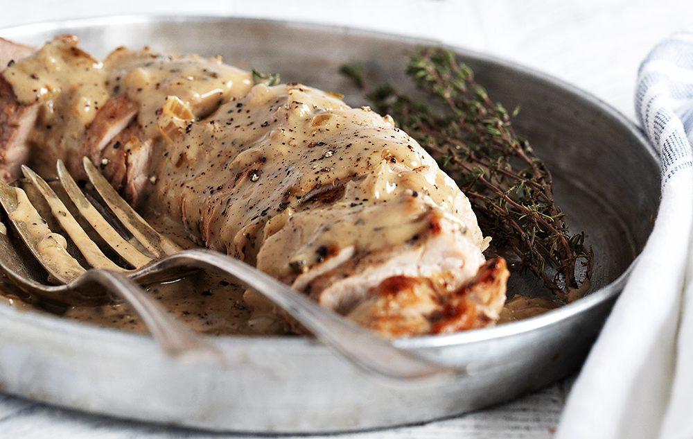 pork tenderloin sliced in pan with peppercorn gravy on top