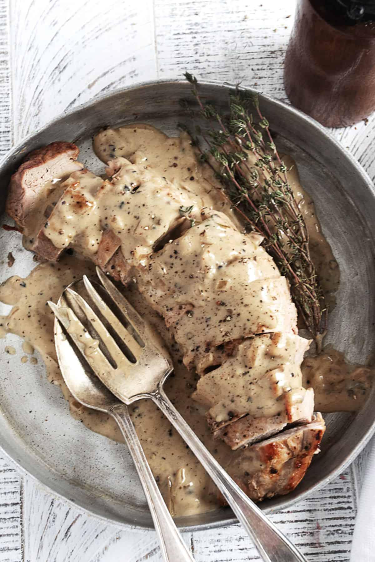 pork tenderloin with peppercorn gravy sliced in pan