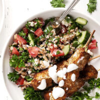 shawarma chicken on skewers on plate with tabbbouleh