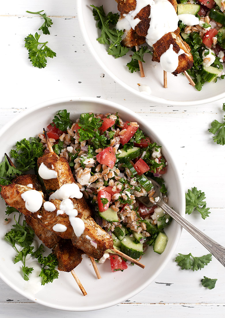 shawarma chicken skewers on top of tabbouleh in white bowls