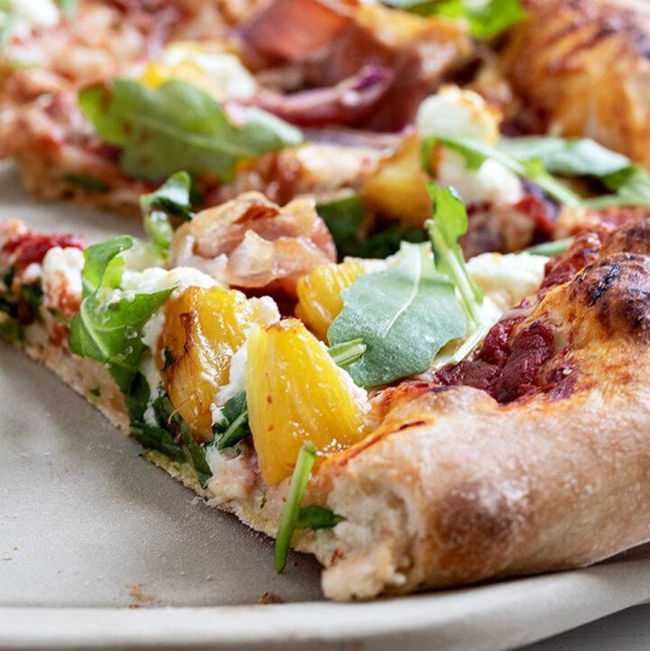 Hawaiian pizza on pizza stone sliced