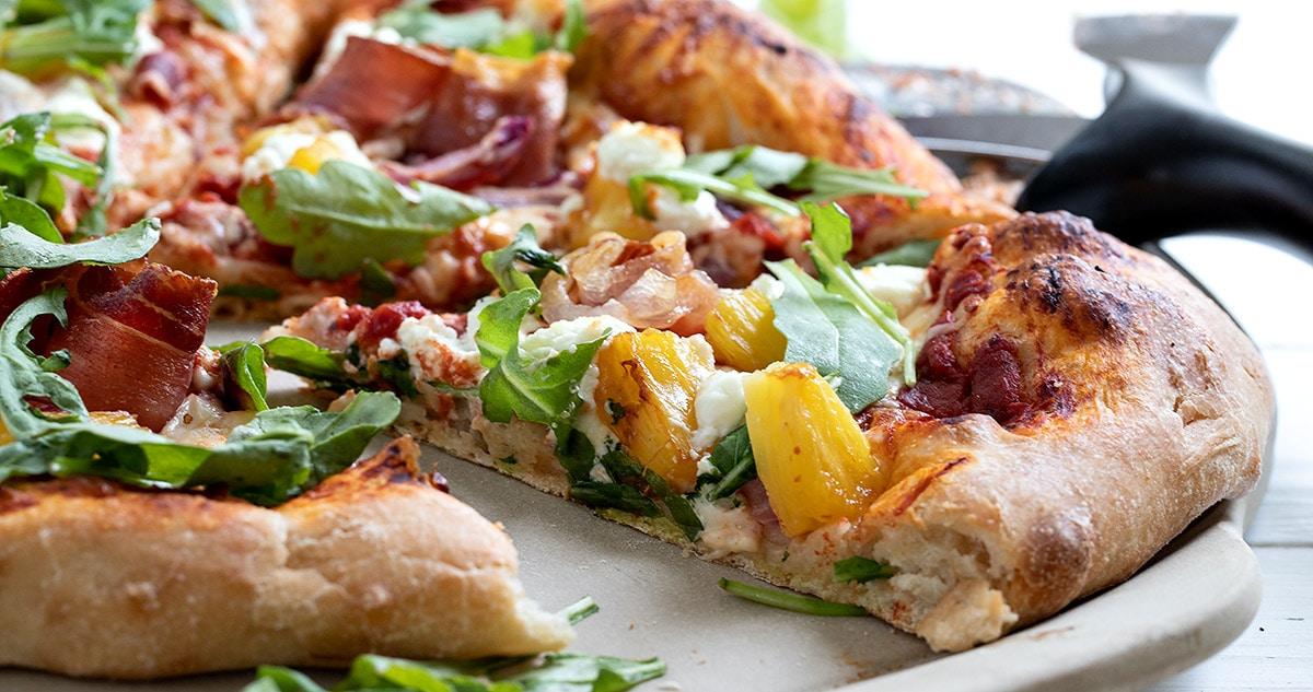 Hawaiian pizza sliced on pizza stone
