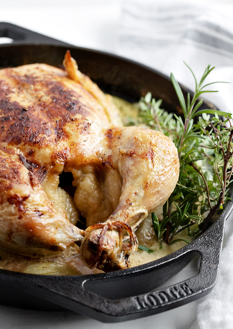 whole braised chicken in skillet with sauce and herbs