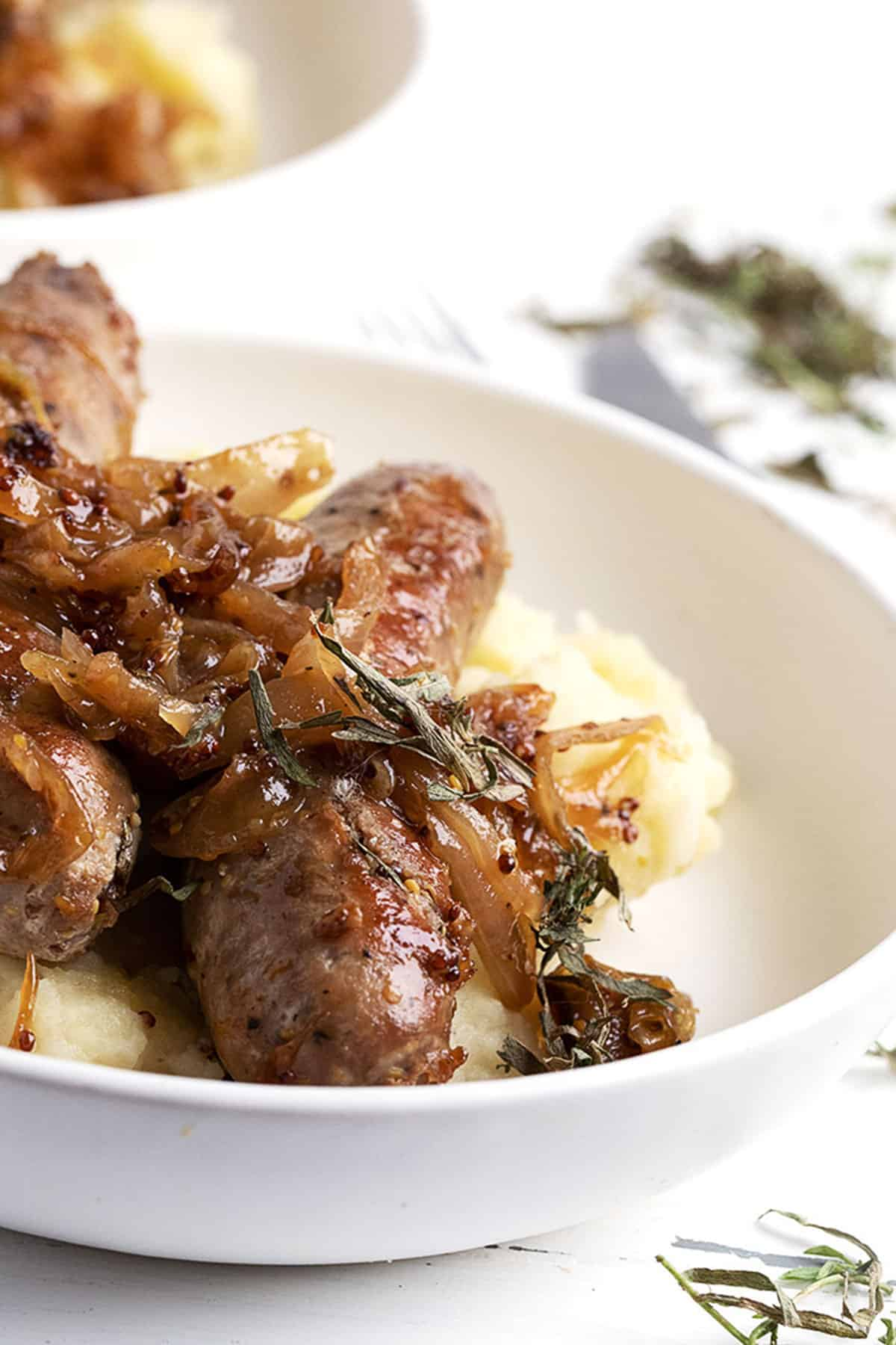 pork sausage in bowl with onions and mashed potatoes