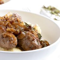 sausage with mustard onions on top with mashed potatoes