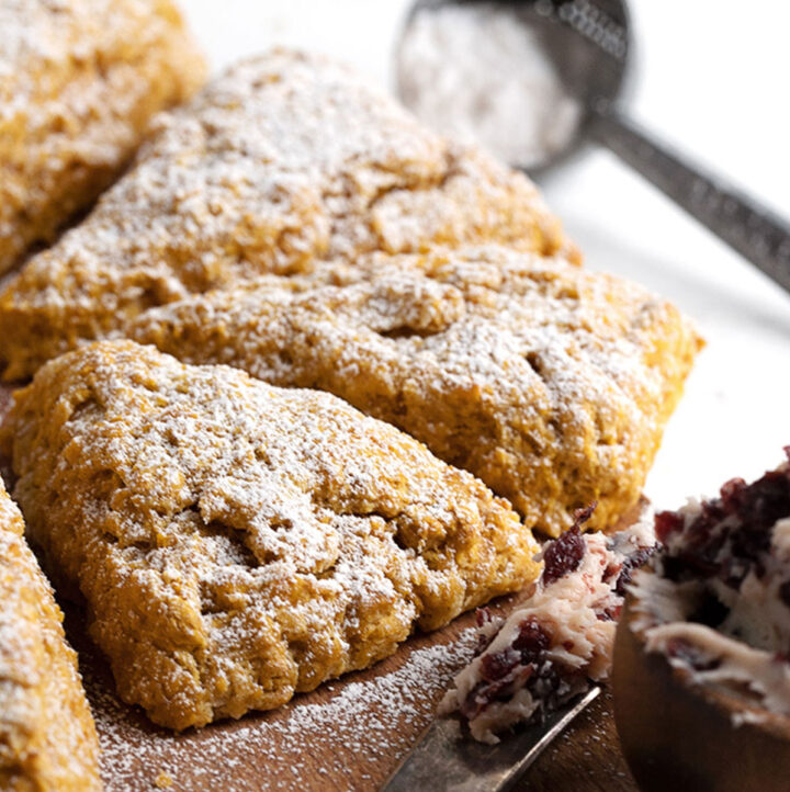 pumpkin scones on cutting board with cranberry butter