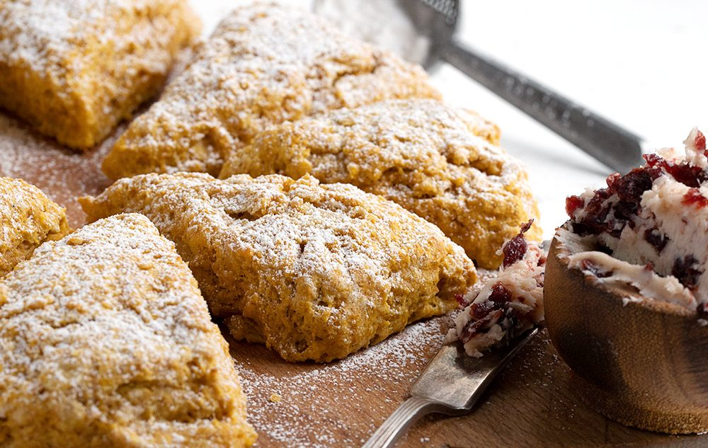 pumpkin scones on cutting board with cranberry butter and knife