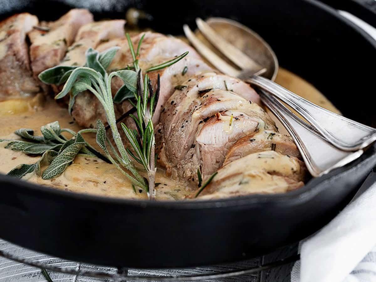 herb and garlic pork tenderloin sliced in cast iron skillet