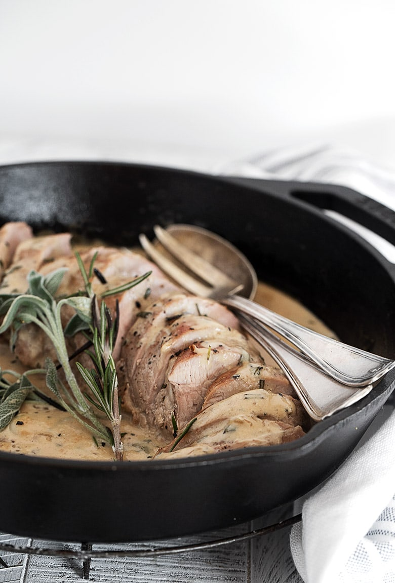 herb and garlic pork tenderloin sliced in cast iron skillet