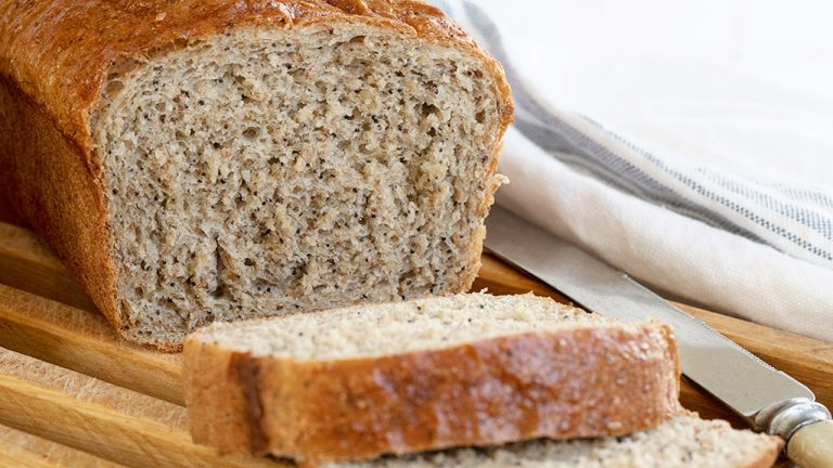 whole wheat bread with seeds, sliced on cutting board