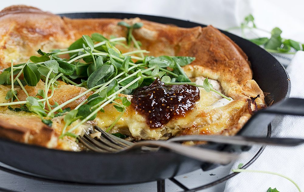 camembert dutch baby in skillet with micro arugula on top