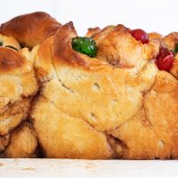 side view of bread with red and green cherries on top