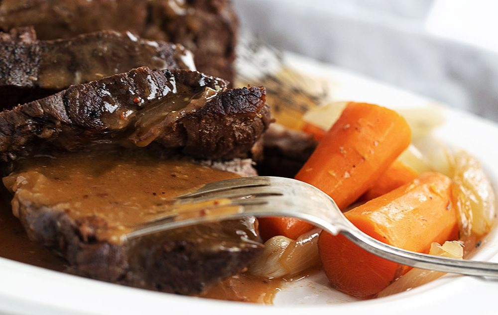 pot roast sliced with gravy, carrots and onions
