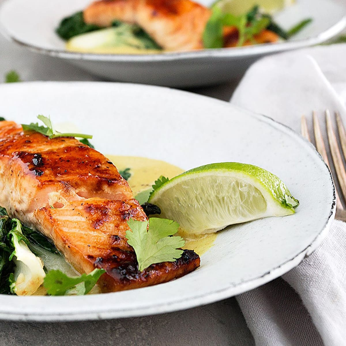 seared salmon in white bowls with lime