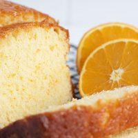 orange drizzle cake loaf, sliced with halved orange