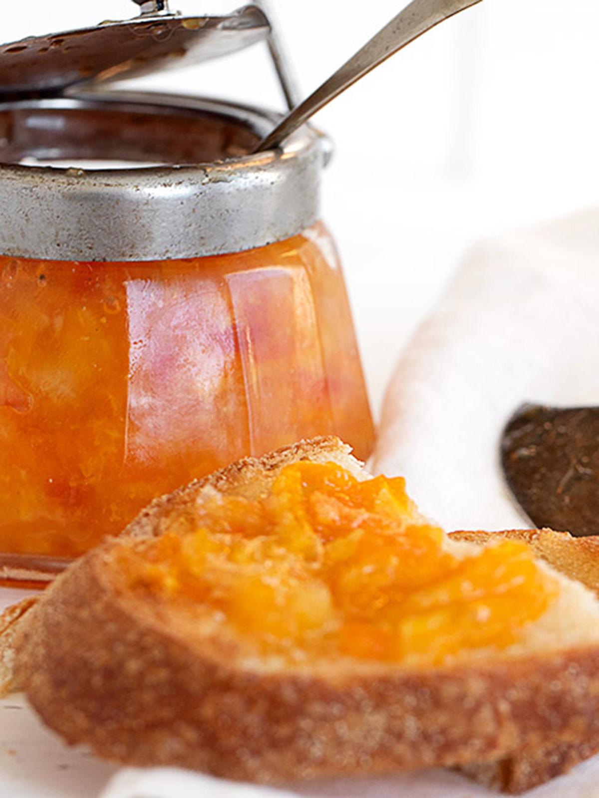 orange marmalade in jar with toast
