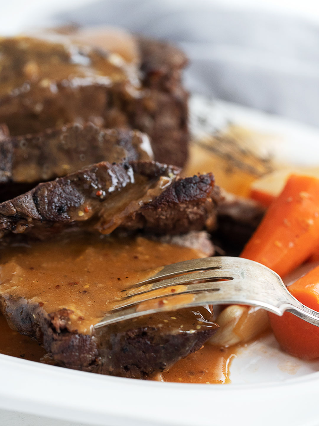 pot roast sliced on plate with gravy, carrots and onion