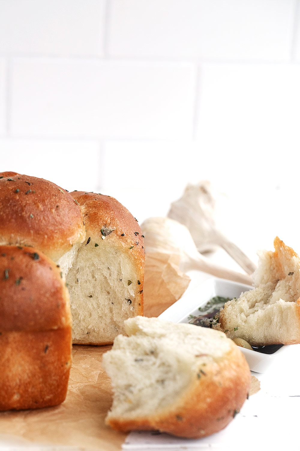 herb and garlic pull apart rolls, with one roll pulled out