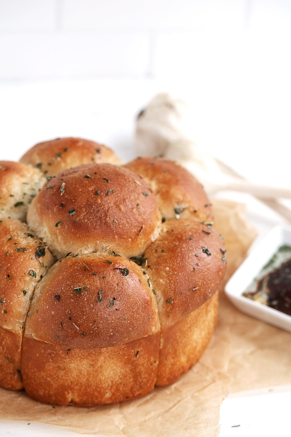herb and garlic pull apart rolls on parchment paper