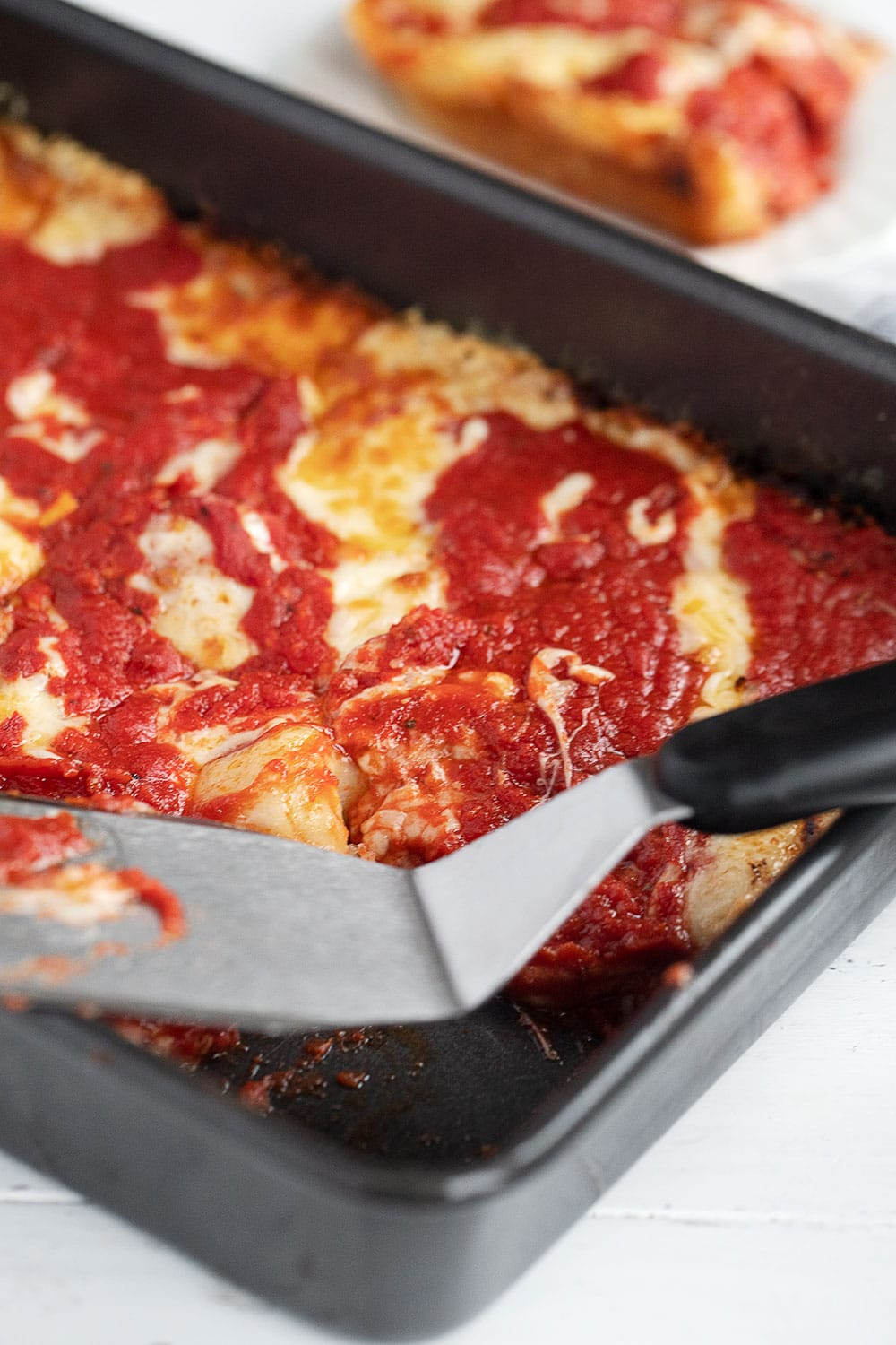 pan of Detroit Style pizza in pan, with spatula