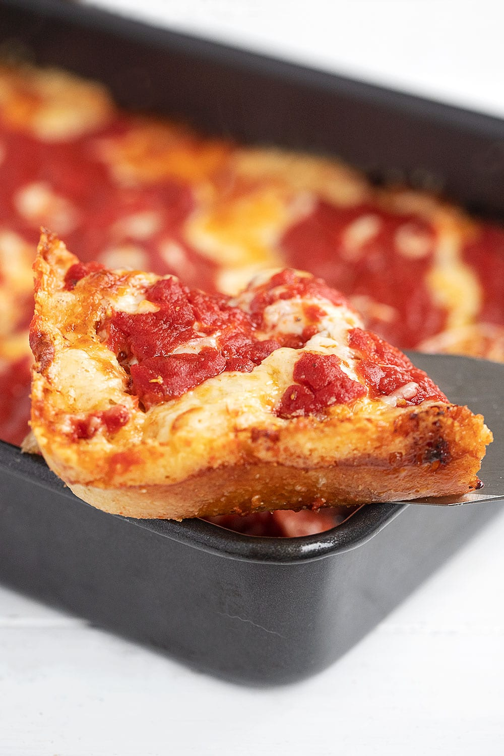 Slice of Detroit Style Pizza on spatula, showing crispy edges