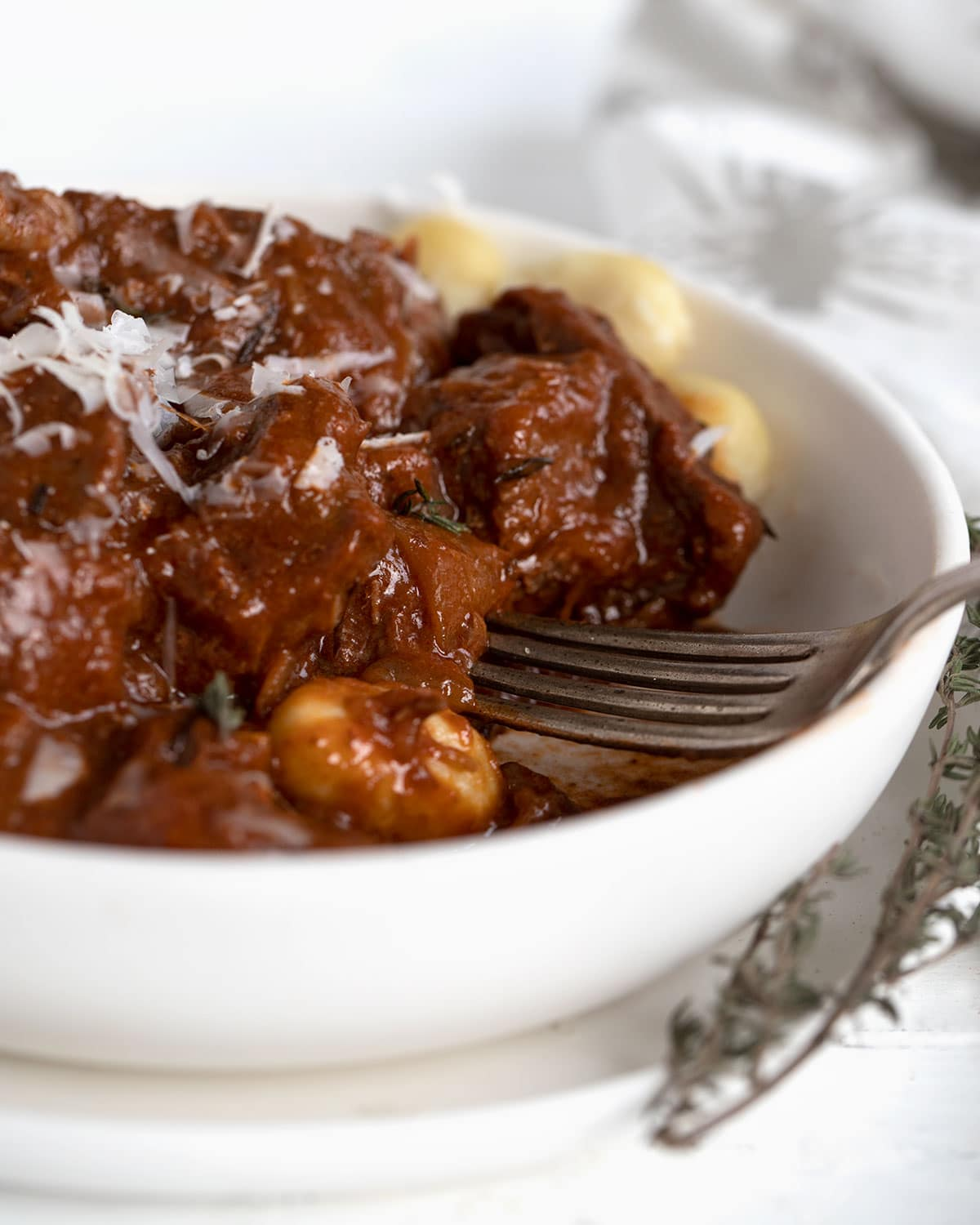 Italian style beef goulash with gnocchi in white bowl with fork
