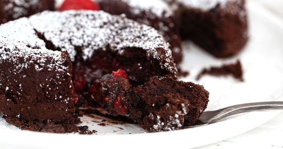 chocolate molten cakes with raspberry filling on plate with fork