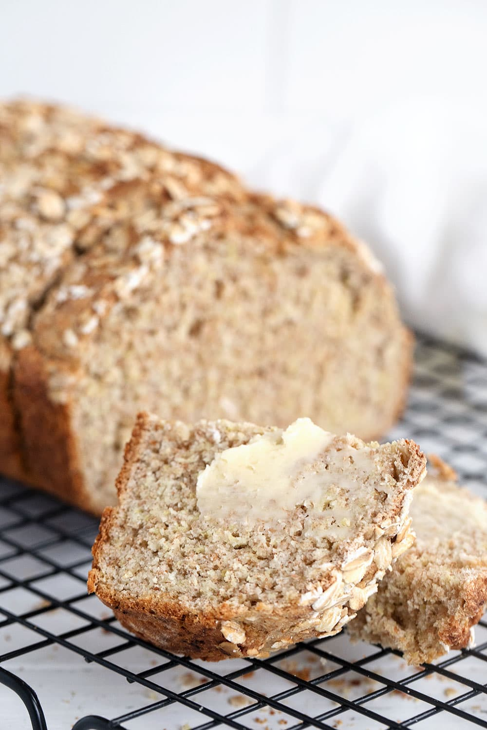 brown Irish soda bread sliced on cooling rack buttered