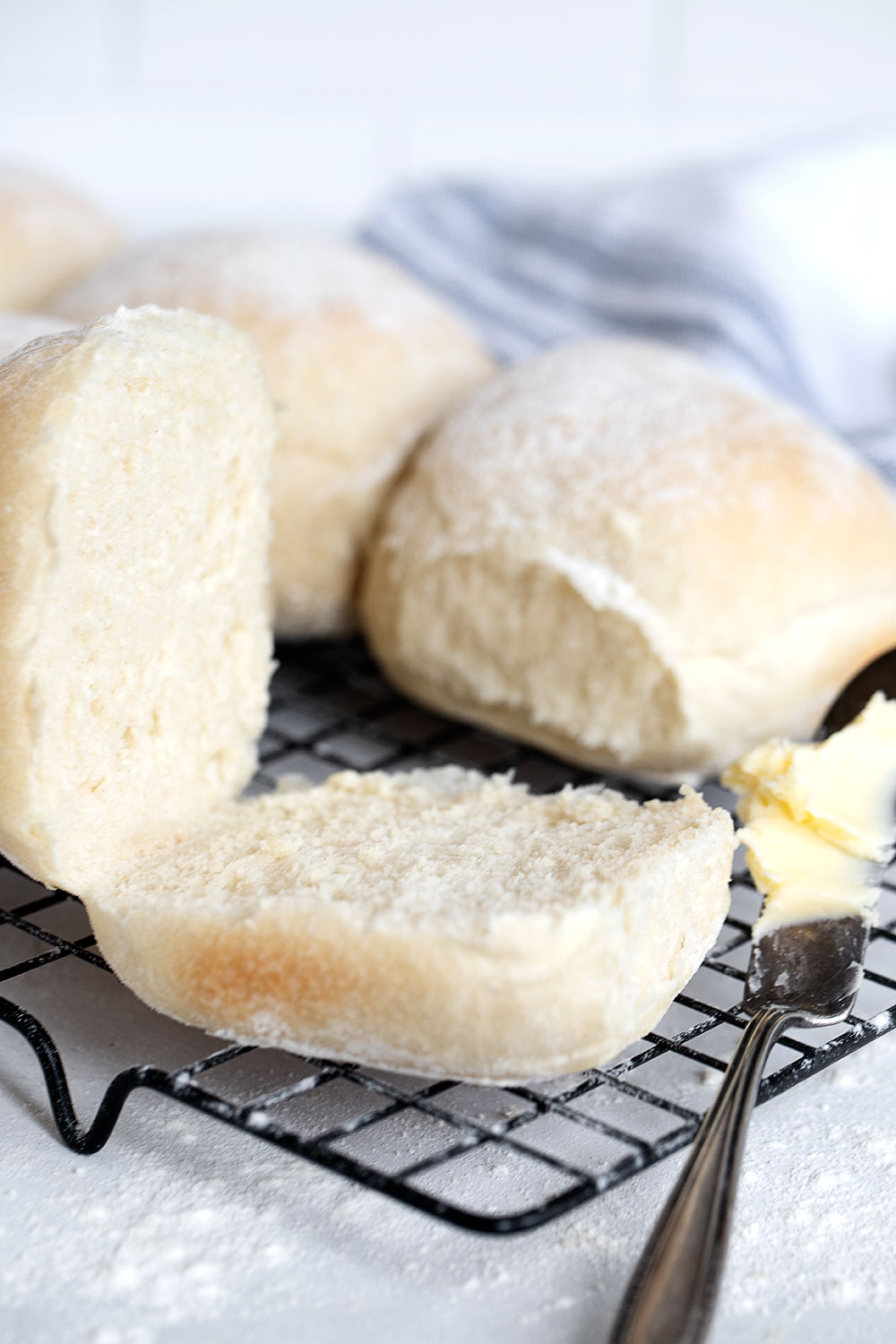 Irish blaa sliced open with butter on cooling rack