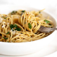 spaghetti with olive oil and garlic in white bowl with fork