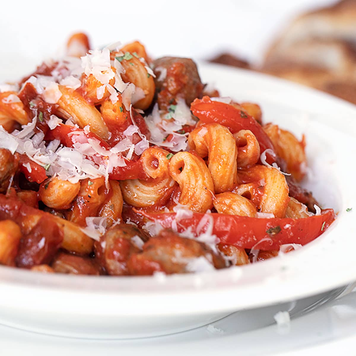 sausage and pepper pasta in white bowl