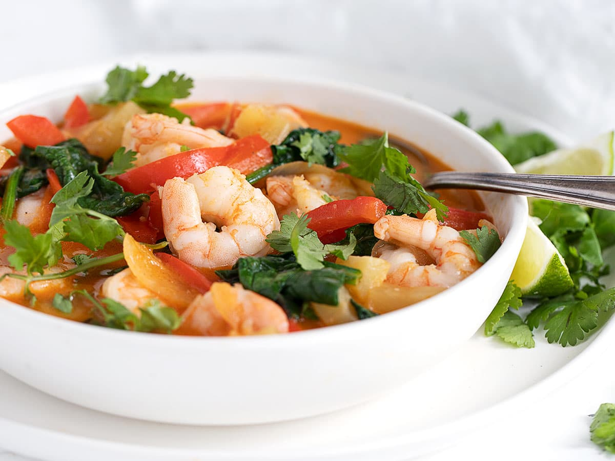 Thai Red Currry Shrimp in white bowl with spoon