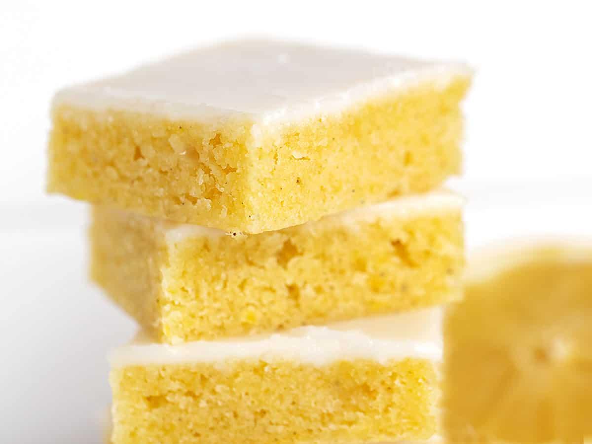 lemon blondies stacked up with lemon slice behind