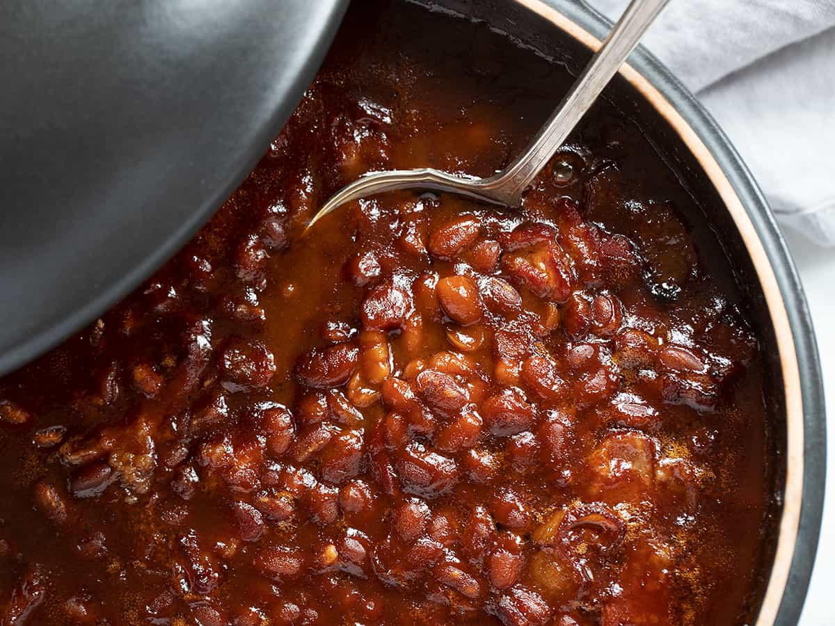 baked beans in black casserole dish with spoon