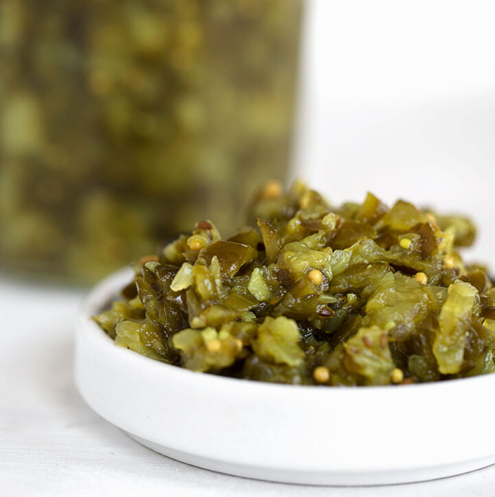 dill pickle relish in bowl with jar of relish behind