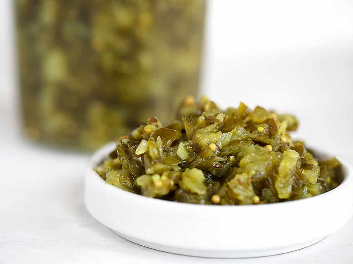 dill pickle relish in white bowl with relish in jar behind