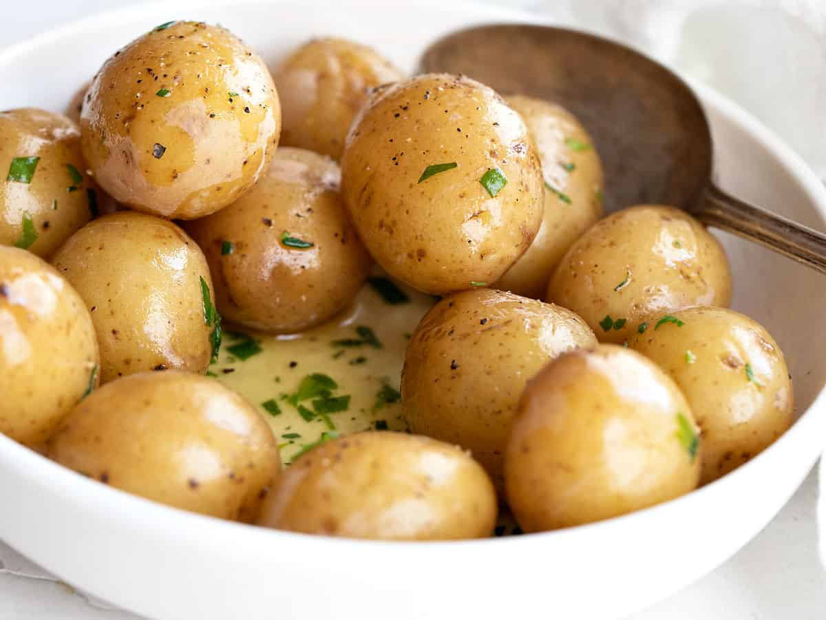 salt potatoes in bowl with melted butter and herbs
