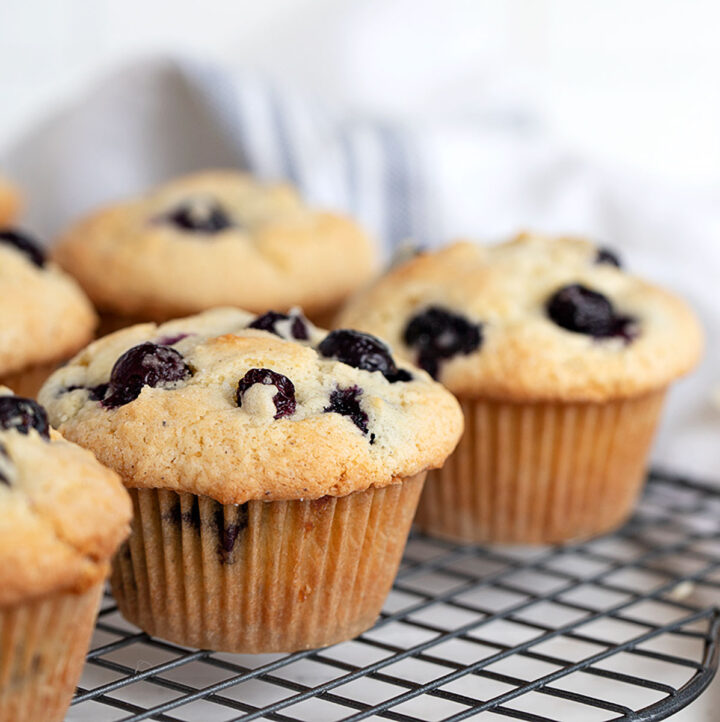 blueberry muffins on cooling rack with knife and butter