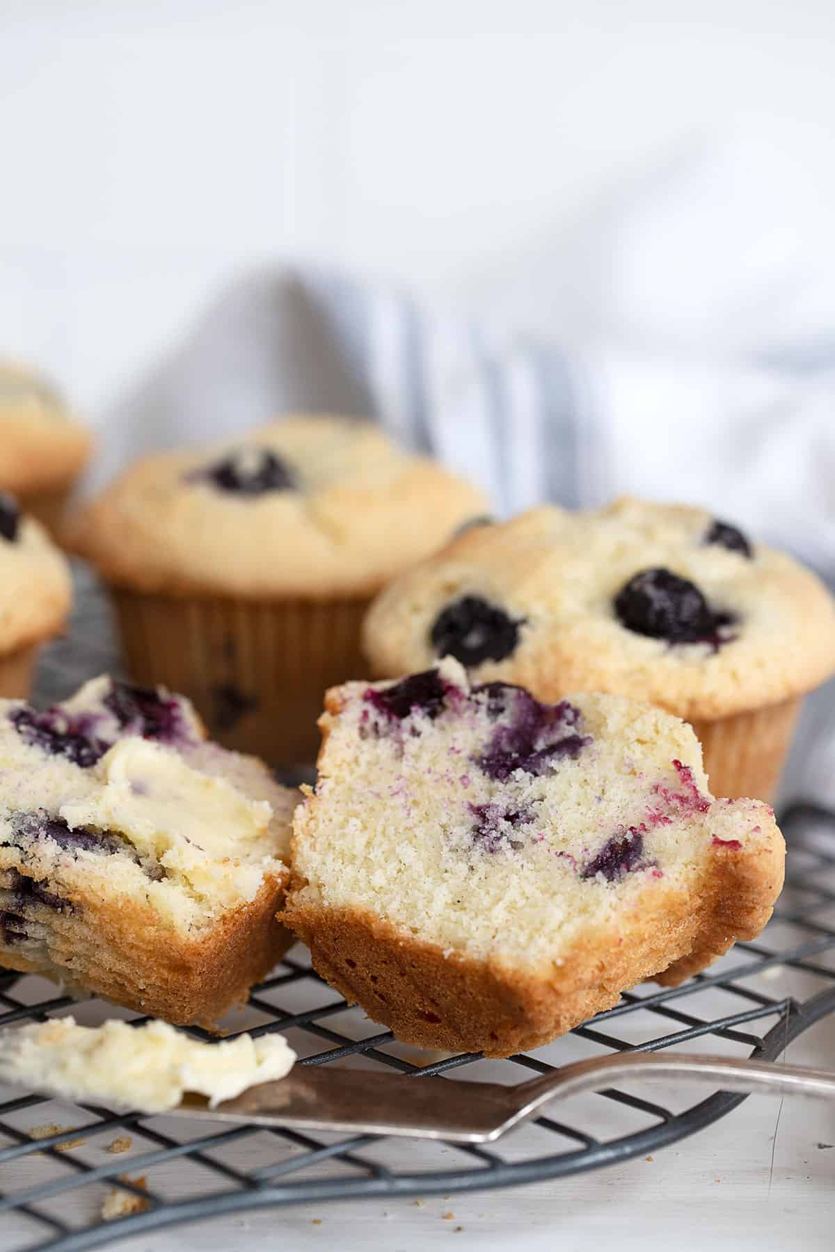 buttermilk blueberry muffins on cooling rack with one cut open and buttered