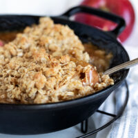 baked apples topped with oat crumble in cast iron skillet