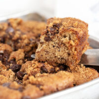 banana chocolate chip snack cake in pan with slice out
