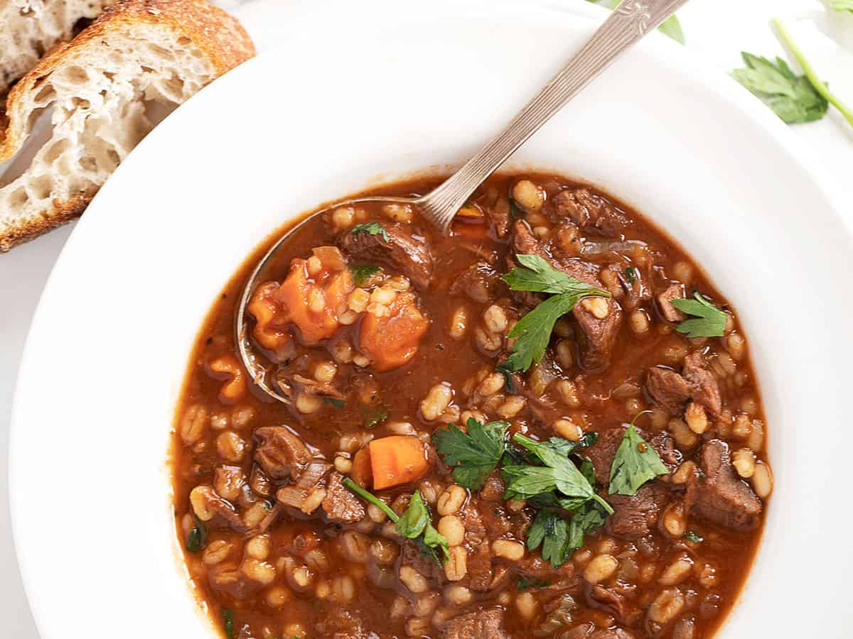 beef and barley soup in bowl with bread on the side
