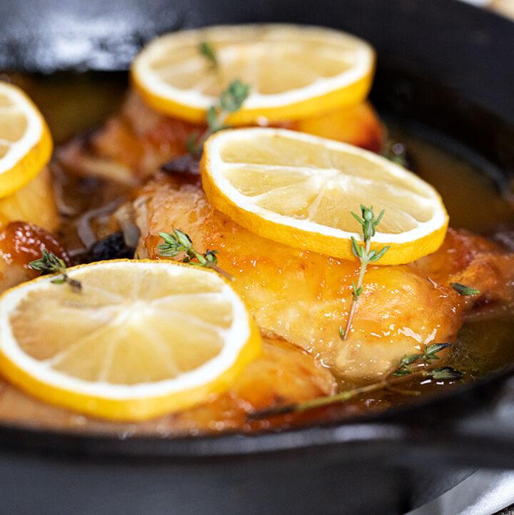 glazed lemon chicken thighs in pan with lemon slices