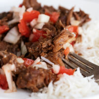 classic pork adobo on plate with rice and tomato onion topping