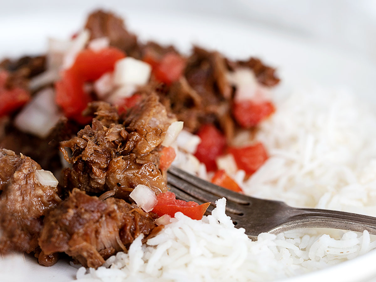 pork adobo on plate with rice and tomato onion garnish