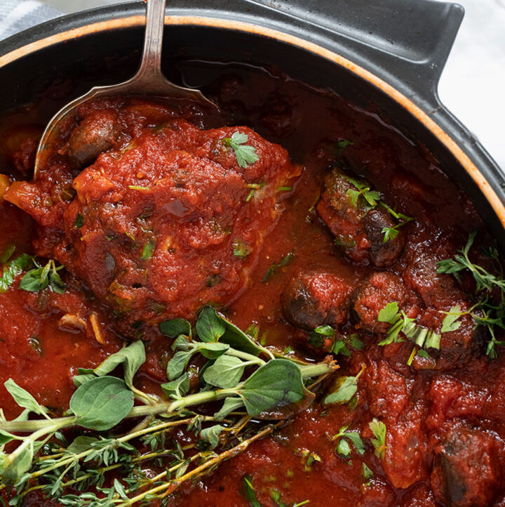 chicken cacciatore in pan with spoon and herbs