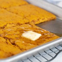 sheet-pan pumpkin pancakes in pan with maple syrup and butter