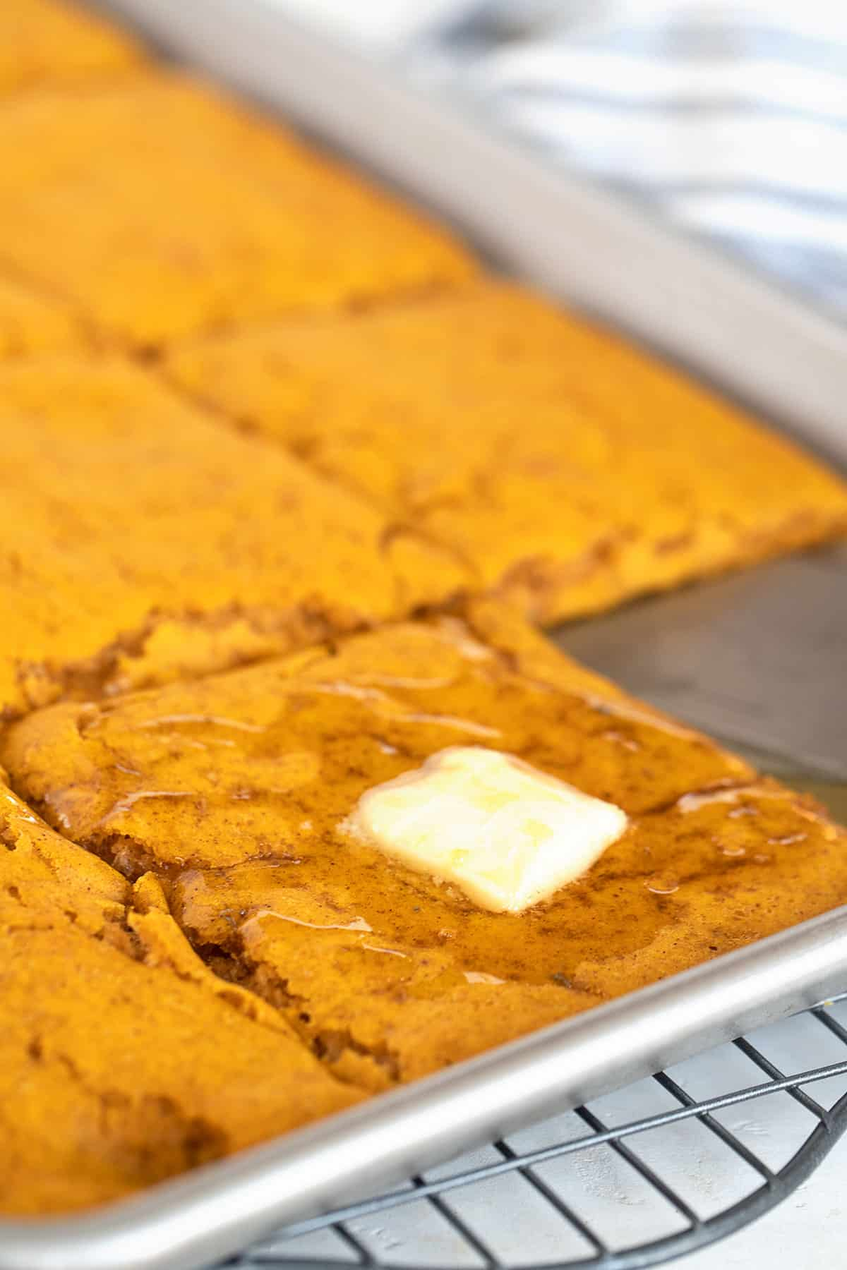 sheet-pan pumpkin pancakes in pan, with butter and maple syrup