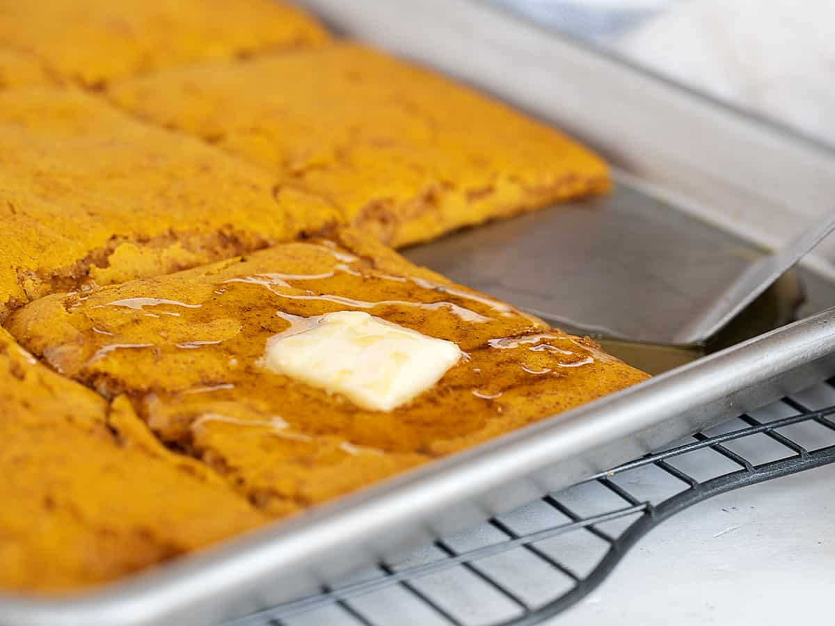 sheet pan pumpkin pancakes in pan with maple syrup and butter